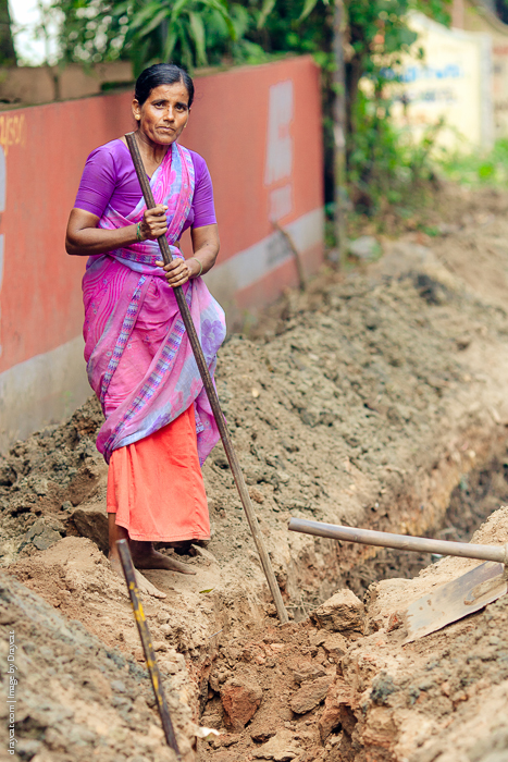 A worker near the trench she is digging, ready to lay pipes.