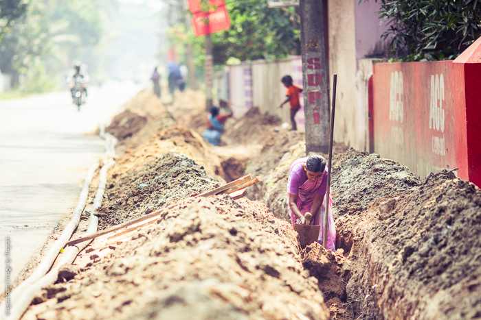 Families digging up the road and laying pipes.